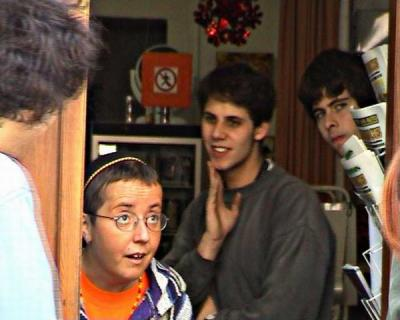 Bára napomíná Miloše, který se při natáčení zapomněl a clonil mamince při vstupu do jejího oblíbeného obchodu. V pozadí druhý režisér Jenda.